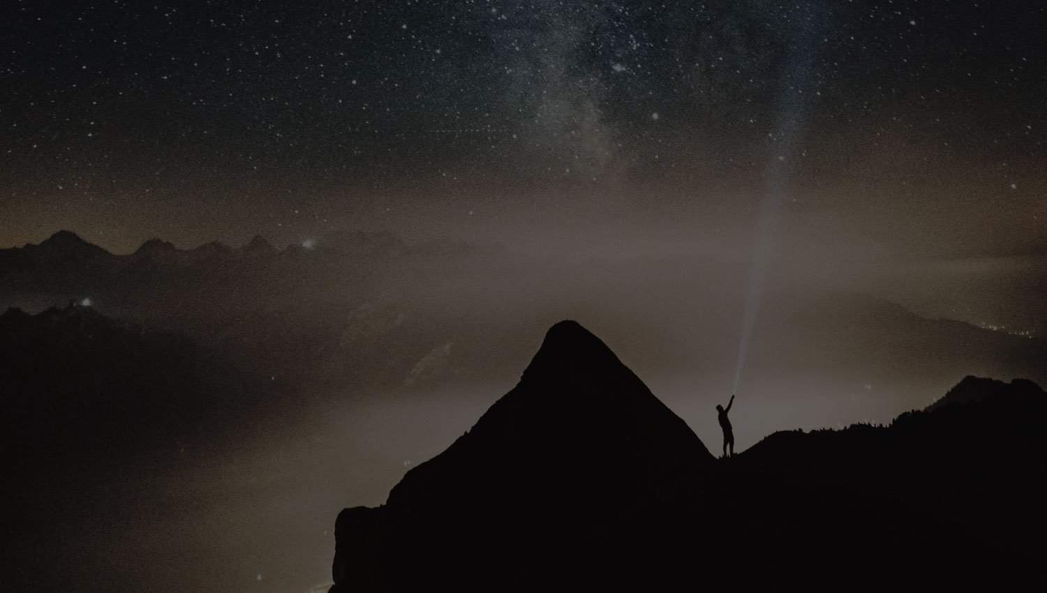 Person standing on top of a mountain, shining a light into the sky
